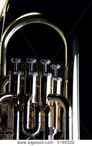 A brass gold bass tuba euphonium against a black background in the vertical format with copy space. poster