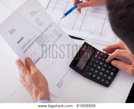 Man Checking An Invoice On A Calculator
