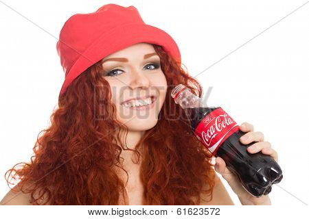 NAKHODKA, RUSSIA - MARCH 02, 2014: Beautiful girl holding a bottle of Coca-Cola. Coca-Cola is a very popular carbonated soft drink sold in stores, restaurants worldwide.