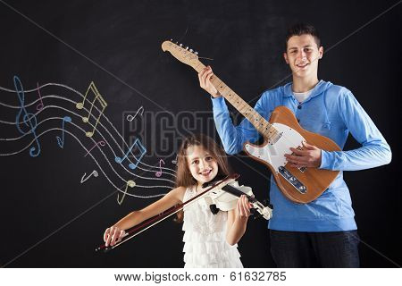 Brother and sister playing a musical instrument next to a blackboard