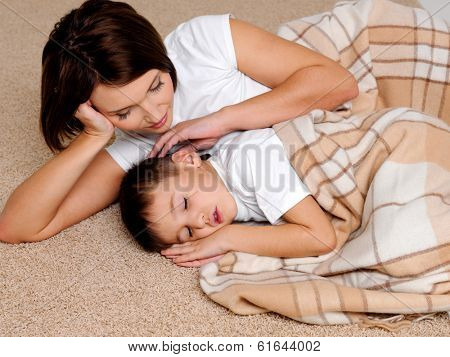 Careful young mum near to the sleeping small son who is covered by a warm plaid