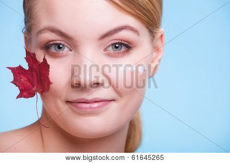 Skincare habits. Face of young woman with leaf as symbol of red capillary skin on blue. Girl taking care of her dry complexion applying moisturizing cream. Beauty treatment. poster