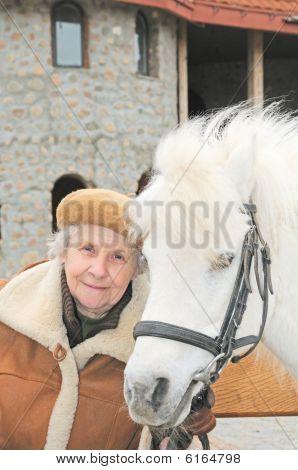 Smiling Elderly Woman Near White Pony