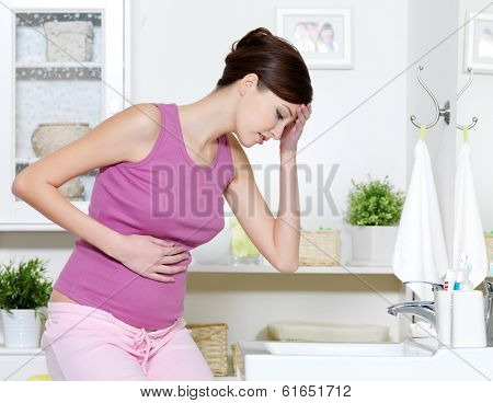 Pregnant woman with strong pain of stomach and nausea sitting in bathroom