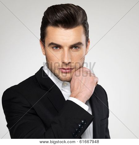 Fashion young businessman black suit casual  poses at studio poster