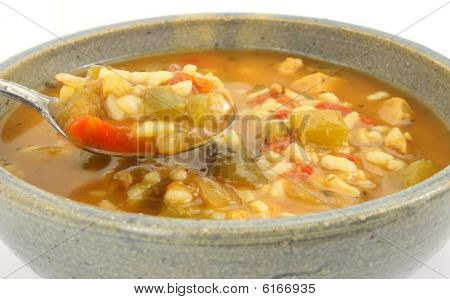 Spicy chicken soup in stoneware bowl with spoon