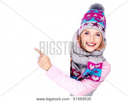 Adult smiling  woman in winter outerwear  holds the white banner in hands and points on it