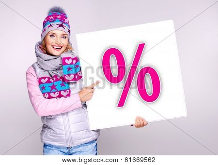 Adult smiling  woman in warm outerwear  holds the white banner with per���ent symbol on it