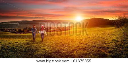 Loving couple holding hands running on the field. beautiful landscape