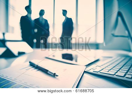 Business devices and documents at the workplace, unrecognized businesspeople sharing the ideas on the background  poster
