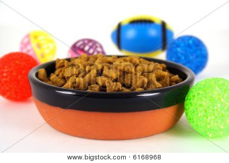 A bowl of pet food surrounded by toys against a white background. poster