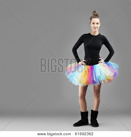 A picture of a happy fashionable woman posing over gray background