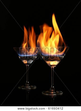Glasses with burning alcohol on black background poster
