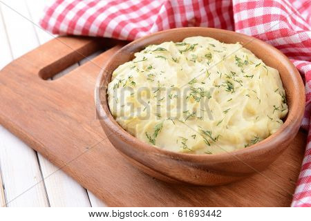 Delicious mashed potatoes with greens in bowl on table close-up