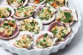 Cooked scallops with cheese and parsley on a platter poster
