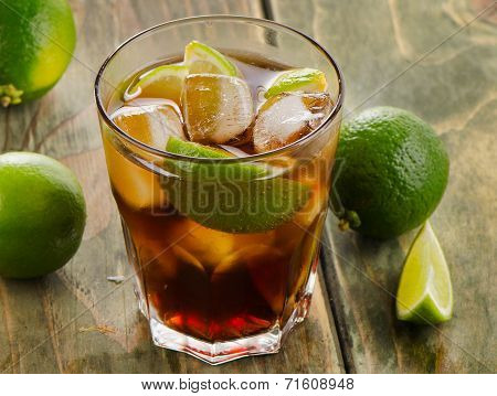 Cuba Libre Cocktail With Limes On A Wooden