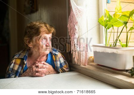 Lonely old woman sitting by the window in his cottage.
