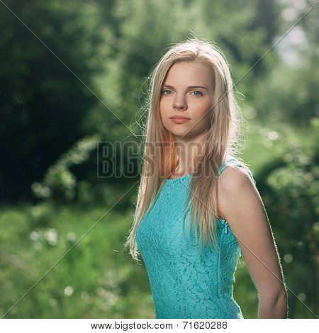 Art portrait of a young cute woman in a turquoise dress with a green forest background