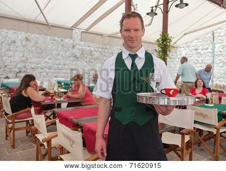 DUBROVNIK, CROATIA - MAY 26, 2014: Waiter in Poklisar restaurant holding tray and posing for camera.Poklisar is popular small familiy restaurant located by the sea.