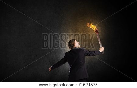 Young businessman holding burning torch in hand poster
