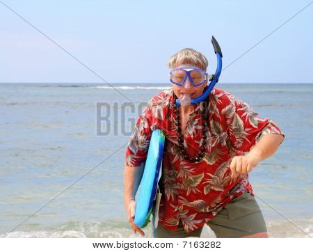 Tourist with snorkel gear and surfboard on a tropical beach