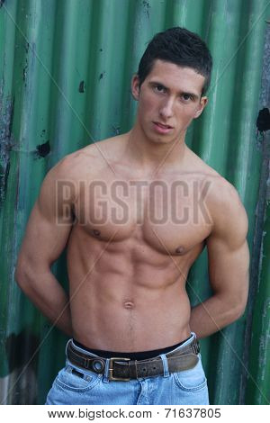 Young muscular man in front of a green crimping metal wall.