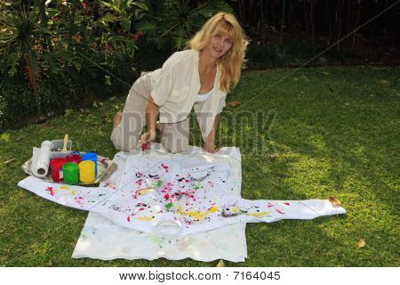 artist in her fifties painting a shirt