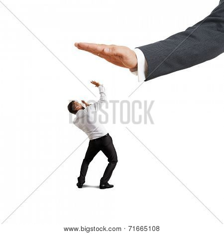 concept photo of conflict between subordinate and boss. scared businessman looking up at big palm of his boss. isolated on white background