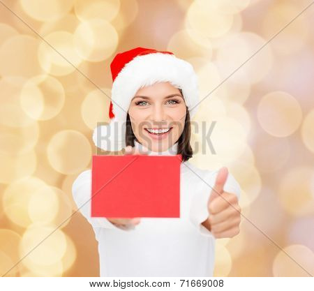 christmas, holdays, people, advertisement and sale concept - happy woman in santa helper hat with blank red card showing thumbs up gesture over beige lights background