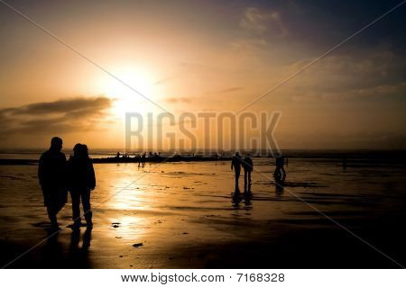 People Silhouetted On A Beach At Sunset