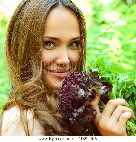 Beautiful slender girl holding healthy fresh greens, toned