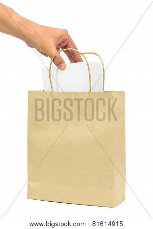 Hand Holding A White Box In Brown Paper Shopping Bags.