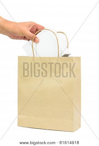 Hand Holding A White Box In Brown Paper Shopping Bag