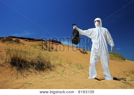 A man in a protective suit holding a bag