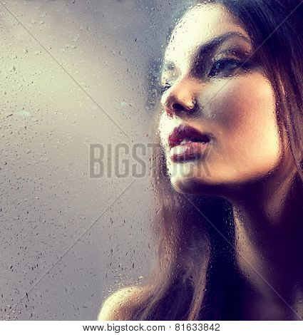 Portrait of Beauty Girl behind the Wet Glass. Melancholy Woman. Rain. Beautiful Model Looking Through the Window with Rain Drops