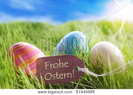 Three Colorful Easter Eggs On Sunny Green Grass With Label With German Frohe Ostern Means Happy East