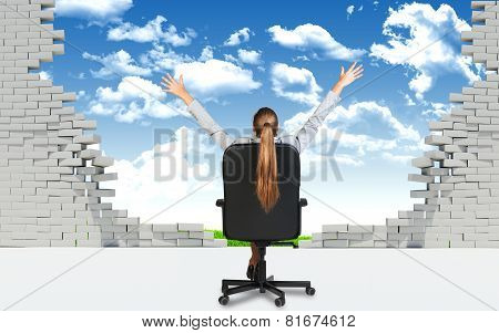 Businesswoman sitting on the office chair in front of broken wall