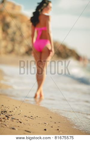 The slender figure of a woman in a bikini on the background of the ocean.