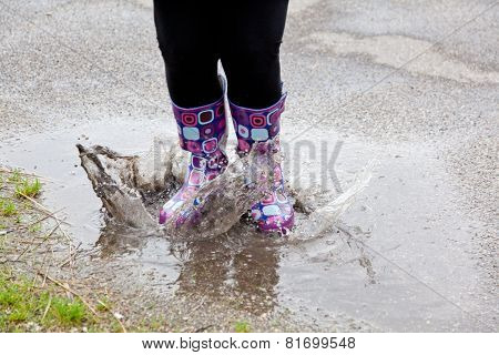 Woman Jumping In A Puddle With Rubber Boots