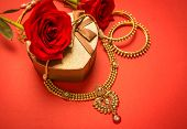 Traditional indian gold necklace and bangles set arranged with heart-shaped gift box and red rose flowers. poster