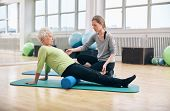Physical therapist working with active senior woman at rehab. Old woman exercising using foam roller with personal trainer at gym. poster