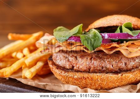 Homemade fast food concept. Mouthwatering french fries and burger. Delicious burger with french fries. Burger and fries on wooden table vintage style. Homemade burger and french fries in dramatic light. Vintage burger or hamburger on old wooden background