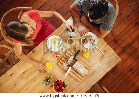 Couple Having Morning Breakfast In Kitchen