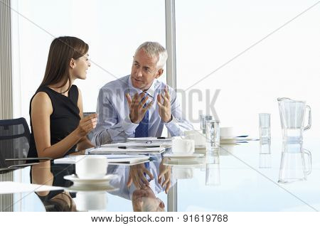 Two Business Colleagues Sitting Around Boardroom Table Having Informal Discussion poster