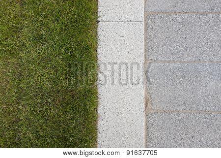 Grey Stone Paving & Kerb Adjacent To Green Grass Lawn