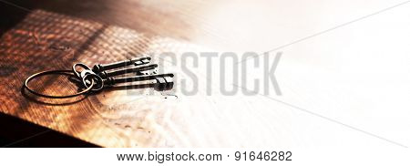 Vintage keys on an grungy old desk with window like shadow fading into white. Shallow depth of focus.