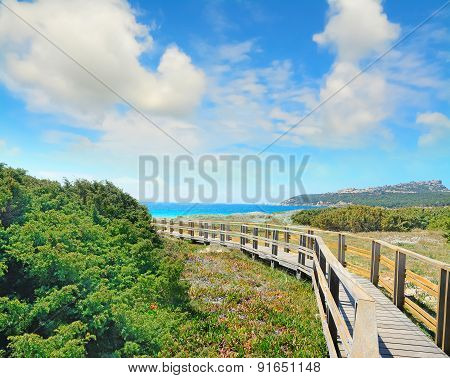 Wooden Boardwalk Under A Cloudy Sky In Capo Testa