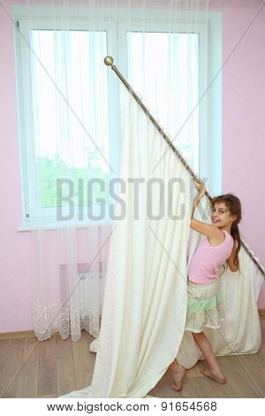 Girl holds the curtain with new draperies at the window in the room