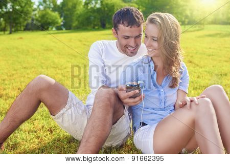 Youth Lifestyle Concept: Laughing Caucasian Couple Sitting Together On The Grass Outdoors With Palmt