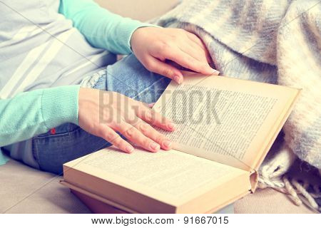 Young woman reading book at home, close-up